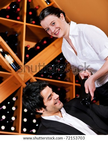 Waitress in a wine bar or restaurant offers a bottle of red wine to a young mediterranean looking man - stock photo