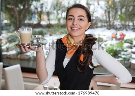 Waitress or server posing with cup of coffee in cafe or restaurant
