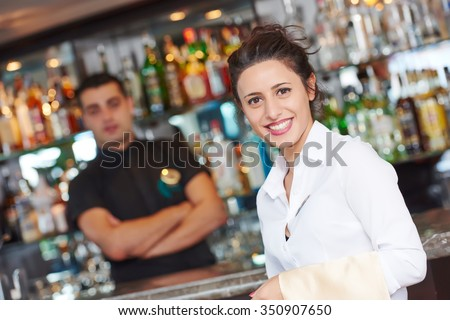 waitress restaurant catering service. Female cheerful restaurant worker with barman at background - stock photo