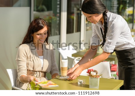 Waitress serve woman latte at cafe bar terrace sunny day - stock photo