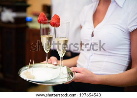 Waitress serving champagne with strawberry on a tray - stock photo