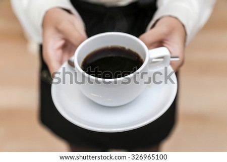 waitress serving coffee cup close up of hand showing coffee - stock photo