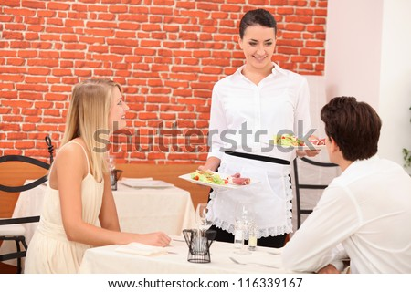 Waitress serving couple