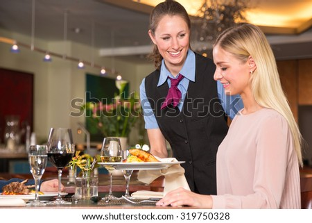 Waitress serving the meal to a guest in restaurant