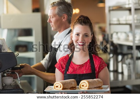Waitress smiling at the camera showing cakes at the cafe - stock photo