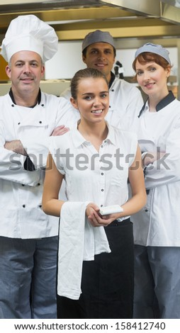 Waitress standing in front of team of chefs smiling at camera