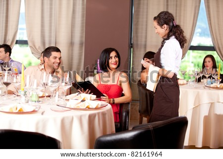 waitress taking dinner order restaurant table young couple - stock photo