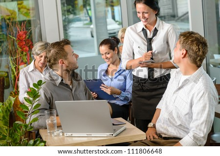 Waitress taking order from businessmen in cafe smiling laptop work - stock photo