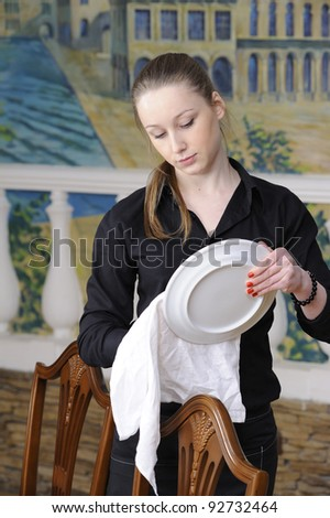 waitress wipes the dishes in restaurant - stock photo