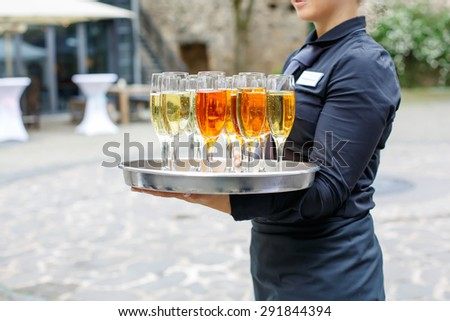 Waitress with dish of champagne and wine glasses. On outdoor wedding reception in summer. - stock photo