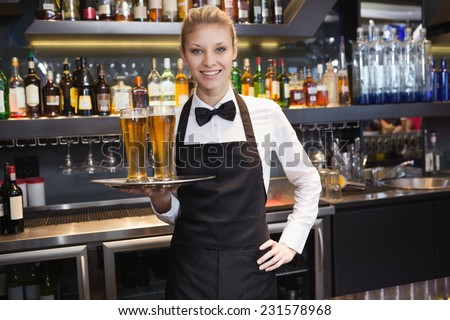 Waitress with hand on hip holding a tray of champagne in a bar - stock photo
