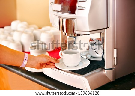 Waitresses hand with coffee machine at cafeteria . - stock photo