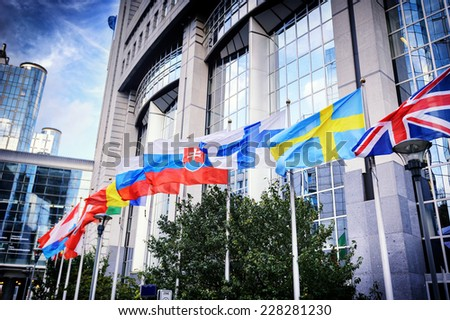 Waiving flags in front of European Parliament building. Brussels, Belgium - stock photo