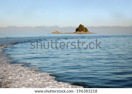 Wake of boat and retreating islands, Abel Tasman National Park, South Island, New Zealand - stock photo
