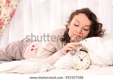 waking pretty young woman lying on bed with white bedding and alarm clock