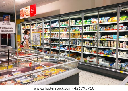 WALDFEUCHT, GERMANY - MAY 11, 2016 : Woman shopping in the refrigerated fresh products aisle of an REWE supermarket, a part of the REWE Group, a German diversified retail and tourism group.