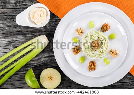 Waldorf Salad with green apples, celery and walnuts on a white dish on a rustic table with ingredients, classic recipe, view from above - stock photo