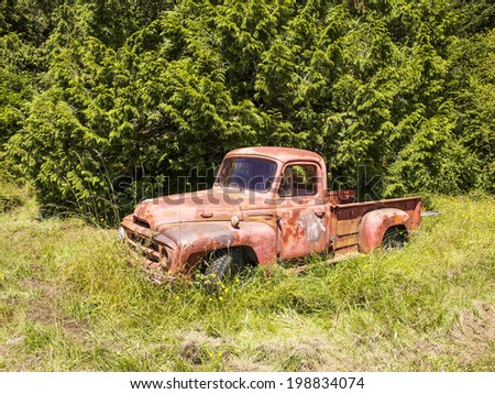WALDRON ISLAND, USA - JUNE 30, 2013:  An old red farm truck is slowly rusting away on a farm on Waldron Island. The rusty truck is emblematic of environmental issues in rural America. - stock photo