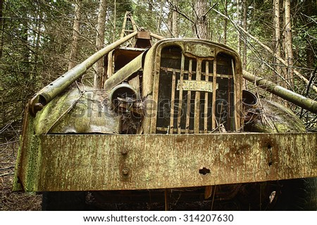 WALDRON ISLAND, USA - MAY 25, 2014: A close-up view from the front of an old, rusted out trash hauler that has been left to decompose in the forest. - stock photo