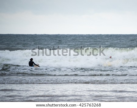Wales, UK - October 22 2015 : A surfer on a cold day looks on as her friend falls of her surf board.