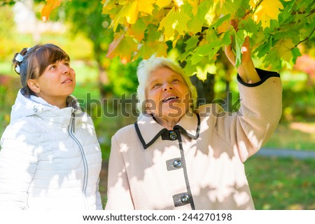 Walk girl with her grandmother in the park in autumn - stock photo