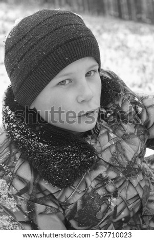 Walk in nature with a boy in the winter. Portrait of a boy wearing camouflage clothes and winter hat.