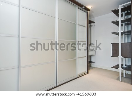 walk in wardrobe with large slide door shrinks and shelf storage - stock photo