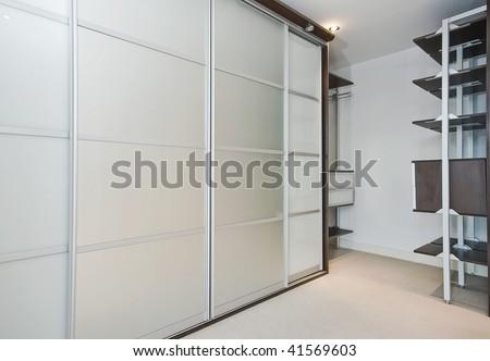 walk in wardrobe with large slide door shrinks and shelf storage - stock photo