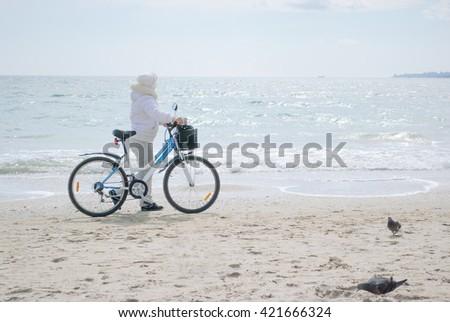 walk on the beach with the bike - stock photo