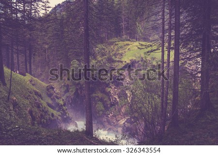 Walk on way mysterious dark old deep rich forest in foggy. Autumn sunny morning day in Austria. Summer. Fairytale. far mountains, hills slope with conifers trees. instagram filter. Magical atmosphere - stock photo
