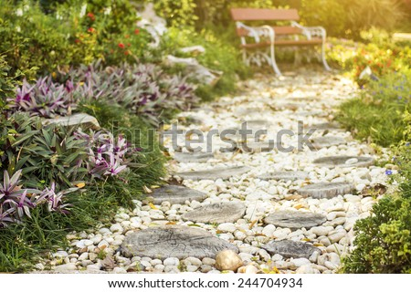 Walk path in garden decorated with stumps and stone to art bench. - stock photo
