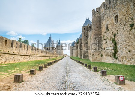 Walk way road in Ancient castle Carcassonne. Ancient fortress with towers and blue sky with clouds in background. Languedoc, France, Europe. - stock photo