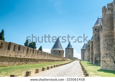 Walk way road in Ancient castle Carcassonne. Ancient fortress with towers and blue sky with clouds in background. Languedoc, France, Europe.