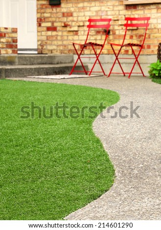 Walk way with perfect grass landscaping with artificial grass in residential area - stock photo