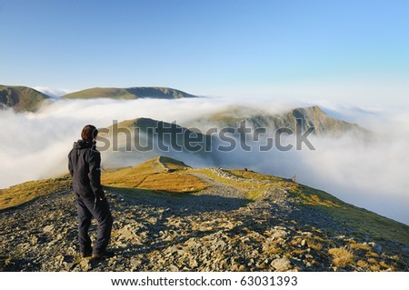 Walker above the clouds on Grisedale Pike, mountain in the English lake District.