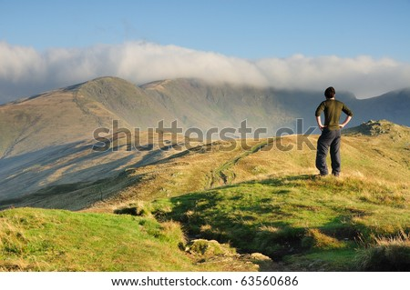 Walker admiring the view towards cloudy Fairfield, mountain in the English Lake District