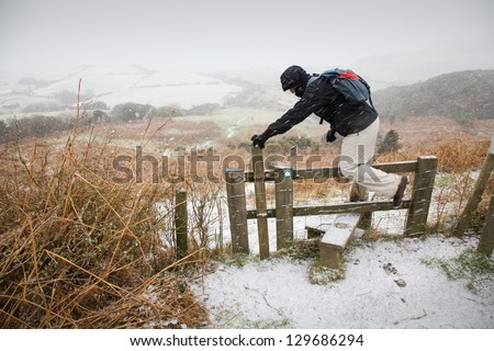walker climbs a stile in the snow in Ravenscar, North Yorkshire, England, UK - stock photo