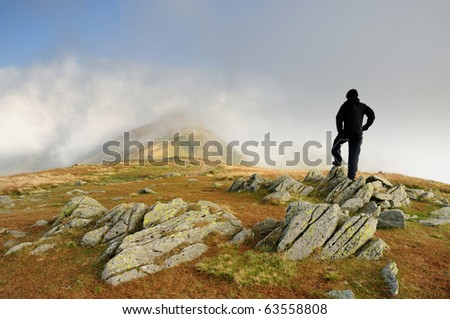 Walker on Great Rigg looking towards Fairfield in the English Lake District - stock photo
