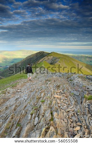 Walker on Whiteside above Gasgale Crags, mountain ridge in the English Lake District - stock photo