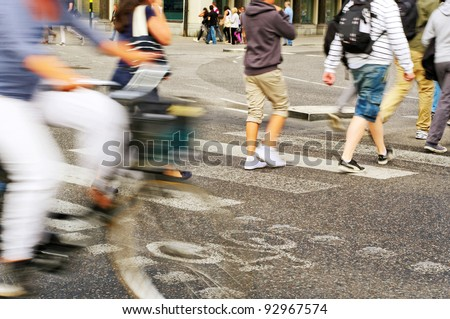 Walkers and biker are crossing a town street. - stock photo