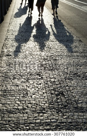Walkers and shadows on the sidewalk, Cobblestones on the pavement - stock photo