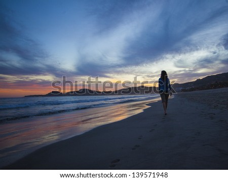 Walking along a tropical beach at sunset - stock photo