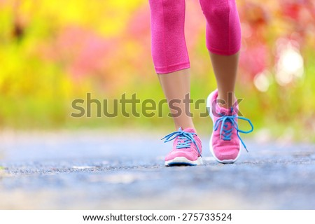 Walking and jogging woman with athletic legs and running shoes. Female walking on trail in forest in healthy lifestyle concept with close up on running shoes. Female athlete jogger training outdoors. - stock photo
