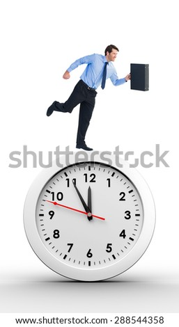 Walking and smiling businessman with suitcase against countdown to midnight on clock