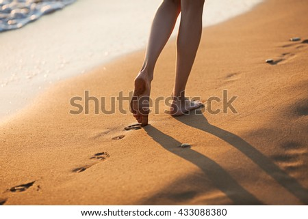 Walking barefoot along the surf on the sand beach at sunset; close up
