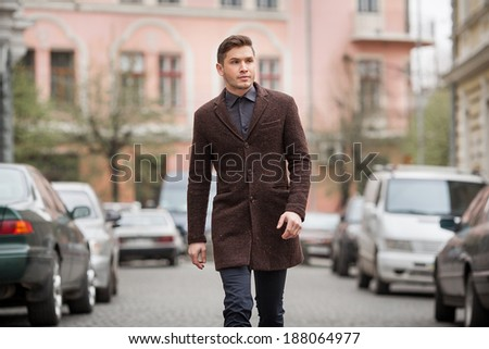 Walking business man. Elegant young handsome man wearing glasses and watchers.