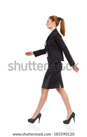 Walking businesswoman in black suit, mini skirt and high heels. Full length studio shot isolated on white. Side view.