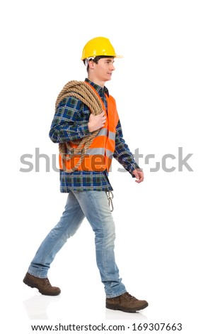 Walking construction worker in yellow helmet and orange waistcoat with rope on his shoulder.  Full length studio shot isolated on white.