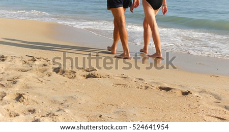 Walking couple on the beach, sunny warm weahter, blue sky an ocean
