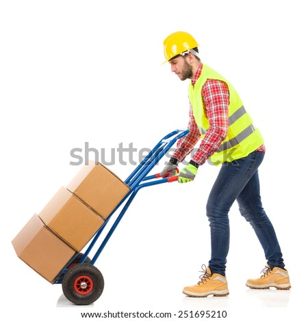Walking delivery man. Serious man in yellow hardhat and lime reflective vest pushing a delivery cart. Full length studio shot isolated on white. - stock photo